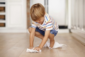 A little boy mopping up a spill at home